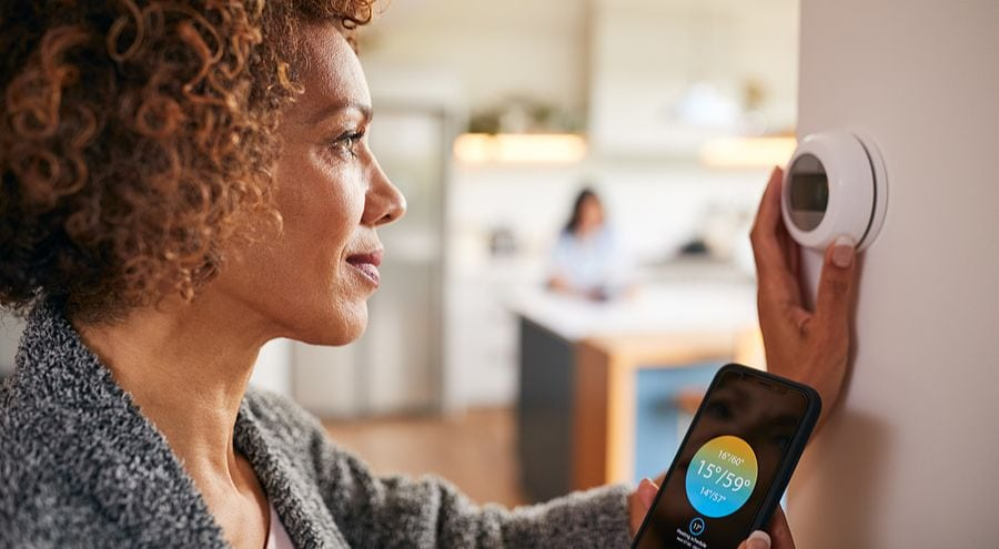 Woman Setting Up Her Smart Thermostat